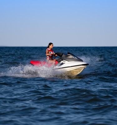 Young brunette in life jacket riding on a jetski